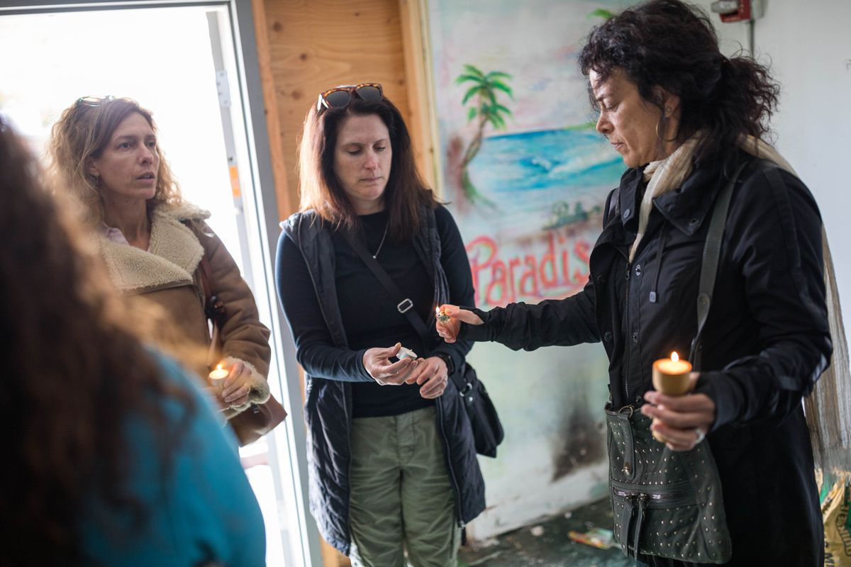 Cindy Berger lights a candle for her friend Julie Wrigley before the group, led by medium Polly Wirum, walked through the former Paradise Inn Friday, May 17, 2019 to