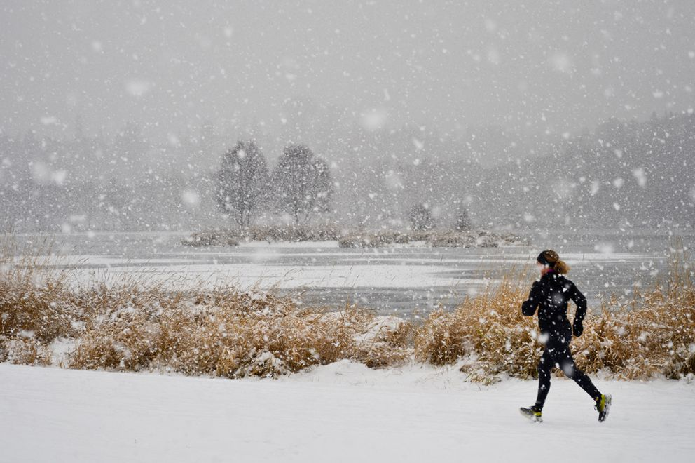 Snow falls near Westchester Lagoon as a runner passes on the Chester Creek Trail on November 16, 2019. (Marc Lester / ADN)