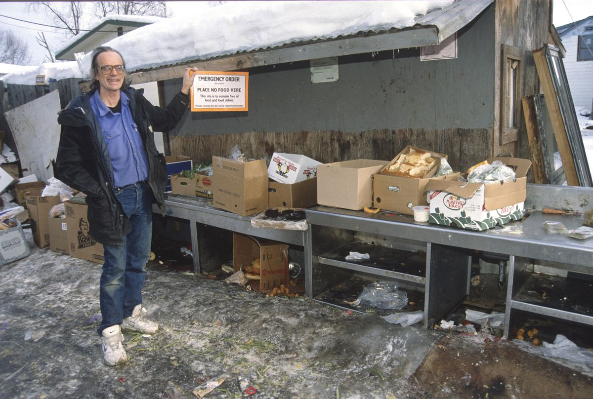 Michael O'Callaghan shows one of the five signs he's torn down from the Earth food give-away tables in the alley in back of his home near Medfra and East 15th Avenue, March 11, 1998. The city health department put the signs up. (Jim Lavrakas / ADN)