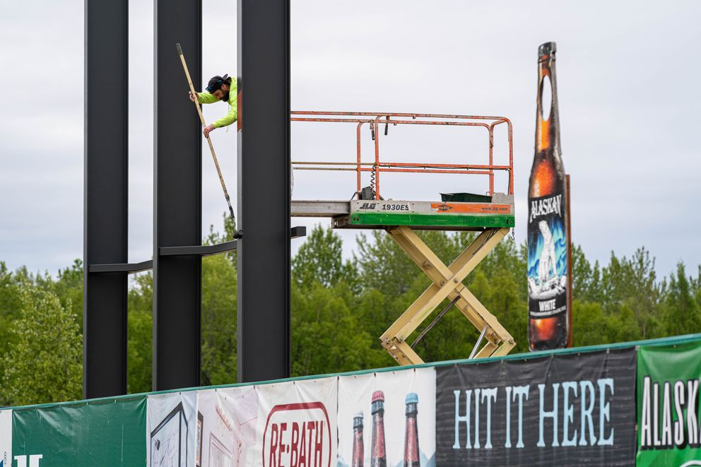Tyler Bales, with Bales Construction, paints a support beam for a scoreboard at Mulcahy Stadium on Wednesday, June 2, 2021 in Anchorage. (Loren Holmes / ADN)