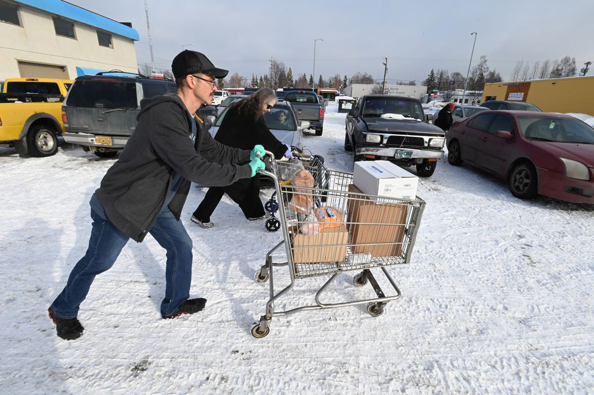 Frank Merculief helped Angel Rickard take food out to a car during the Lutheran Social Services of Alaska food pantry distribution in Spenard on Wednesday, March 18, 2020. (Bill Roth / ADN)