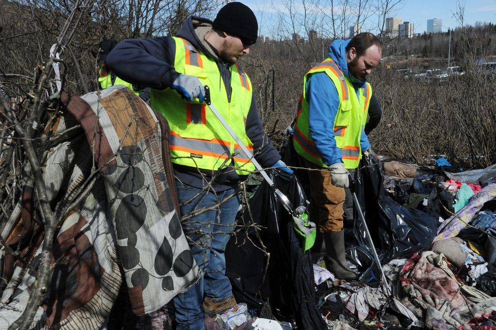 Municipal Parks & Recreation maintenance workers Michael Wayne Connor, Jr., left, and Kyle Leddy remove debris from an abandoned homeless camp nestled between the Hillcrest Drive offramp and Minnesota Drive on Thursday, April 25, 2019. (Bill Roth / ADN)