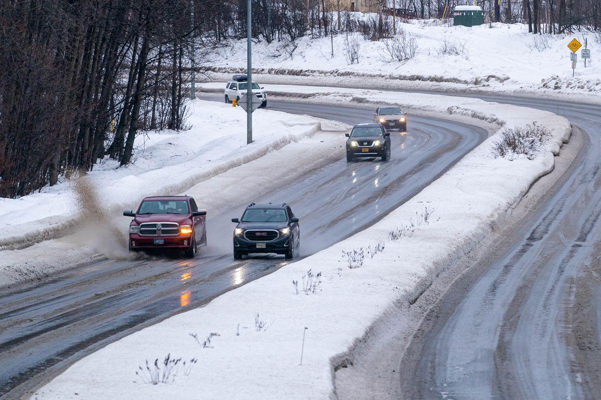 Vehicles drive through standing water on Northern Lights Boulevard near East High School on Monday, Jan. 18, 2021. (Loren Holmes / ADN)