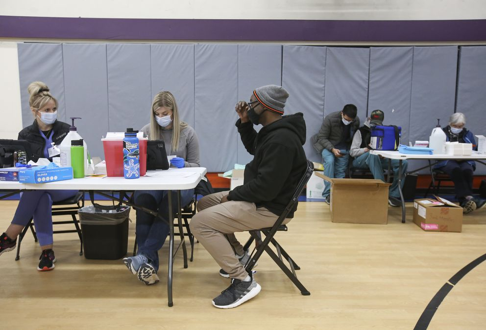 Marquis Hiriams talks with nurses Kadie Hansen and Crista Johnson before getting his first dose of the COVID-19 vaccine at The Alaska Club West. (Emily Mesner / ADN)