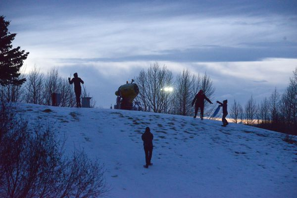 An idle snow gun sits on the top of the sledding hill at Kinciad Park in Anchorage, Alaska on Tuesday, Jan. 2, 2018. Hanna Craig is on skis as Carol Holts reaches out to help Tchavo Acemah and Heather Craig walks up the hill. The temperature reached 46 degrees in Anchorage on Tuesday. (Bob Hallinen / ADN)