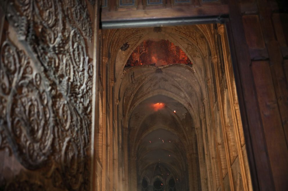Smoke and flames are seen in the interior of Notre Dame cathedral in Paris, Monday, April 15, 2019. A catastrophic fire engulfed the upper reaches of Paris' soaring Notre Dame Cathedral as it was undergoing renovations Monday, threatening one of the greatest architectural treasures of the Western world as tourists and Parisians looked on aghast from the streets below. (Philippe Wojazer/Pool via AP)