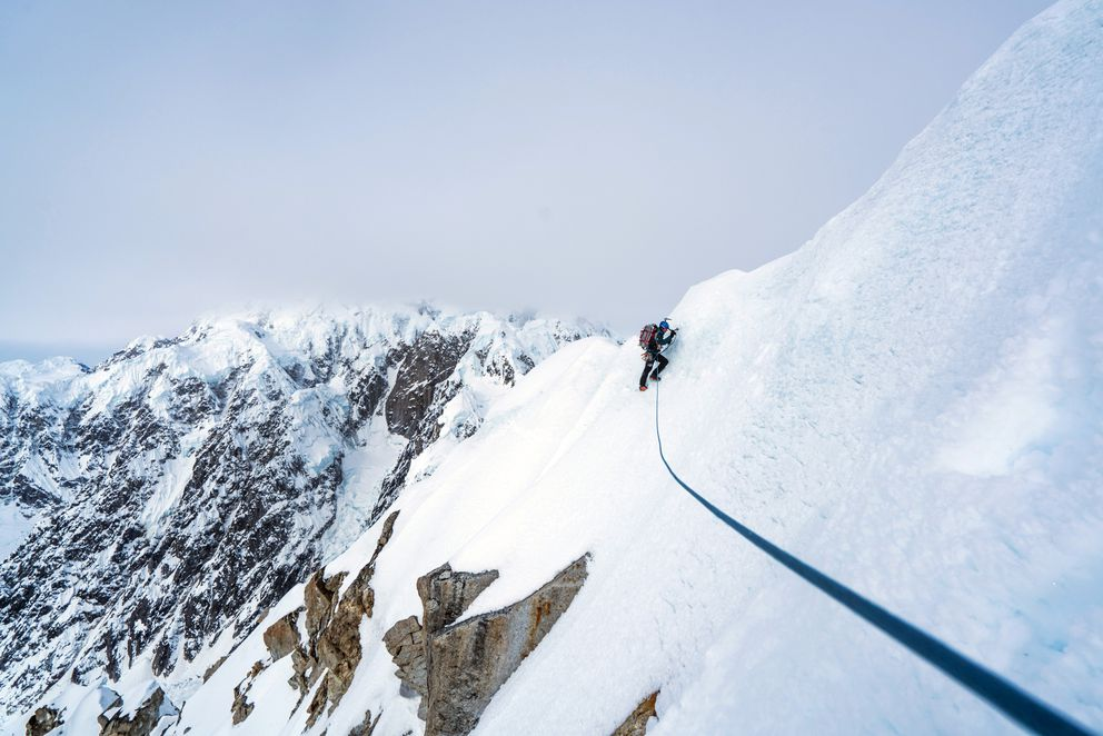 Jess Roskelley navigates the summit cornices of Idiot Peak hours before he and Clint Helander topped out on their climb of the South Ridge of Mount Huntington. Variable snow conditions forced the team to traverse large sections of the mountain with scant protection. (Photo by Clint Helander)