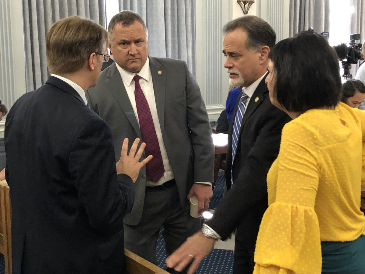Deputy Attorney General John Skidmore, left, speaks to Sens. Mike Shower, R-Wasilla; Peter Micciche, R-Soldotna; and Shelley Hughes, R-Palmer; during a break in the Sunday, May 12, 2019 Senate Finance Committee meeting. (James Brooks / ADN)