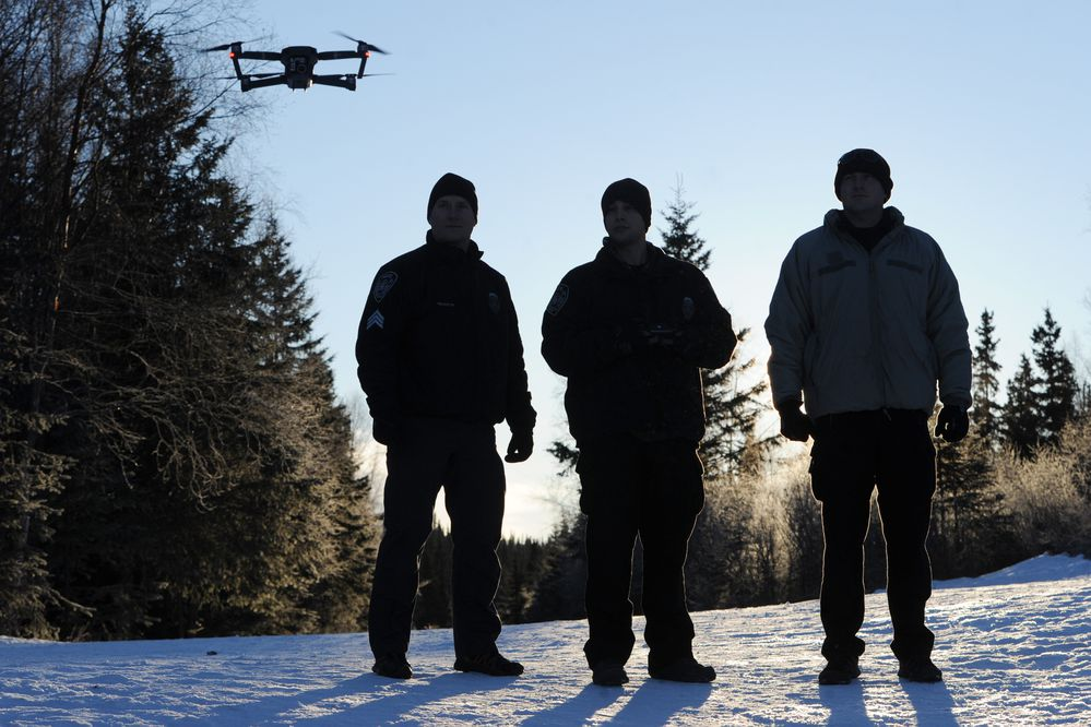 APD Sgt. Mark Huelskoetter, left, and Officer Jeremy See, right, watch as Officer Erik Jensen landed a drone during a training flight on Tuesday, Jan. 15, 2019. The officers are FAA-certified drone pilots and members of the technical support unit for APD's SWAT team. They flew the drone over Far North Bicentennial Park and looked for the missing rodeo cow named Betsy which simulated a search-and-rescue mission while logging cold weather flight time. (Bill Roth/ ADN)