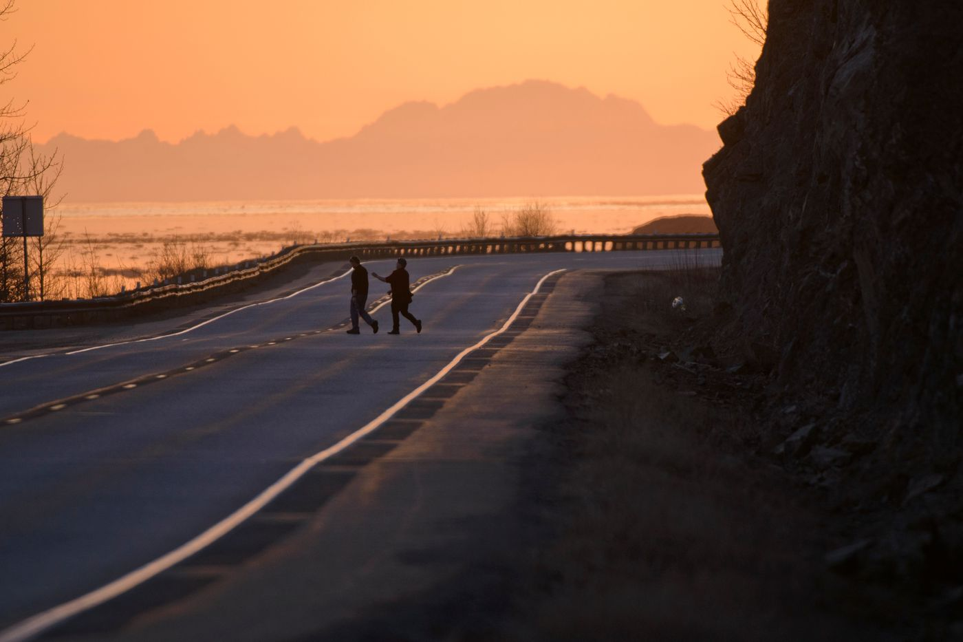 Two people cross the Seward Highway at Mile 109 after filling small water bottles a week ago. (Marc Lester / Alaska Dispatch News)