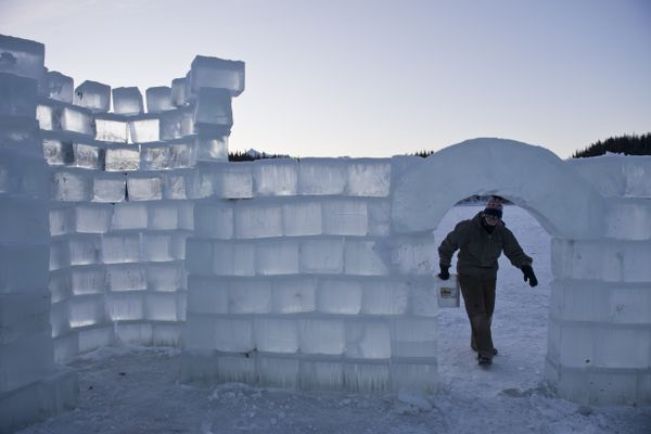 Intern Hannah Primm carries a bucket of snow to help fill in some spaces. Employees and interns of Victory Bible Camp created a castle-themed shelter from ice block on Index Lake in the Glacier View area. Most of the work was done in a day two week ago, but improvements were ongoing on Dec. 1, 2017. (Marc Lester / ADN)
