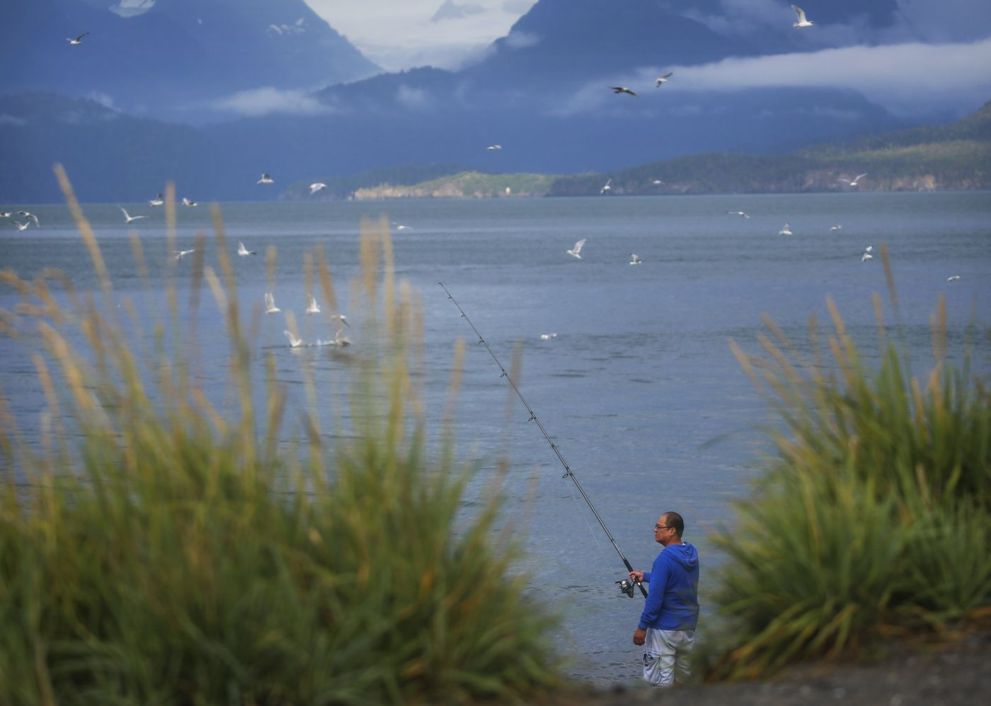 A man fishes on the beach at the end of the Homer Spit on Aug. 8, 2020. (Emily Mesner / ADN)