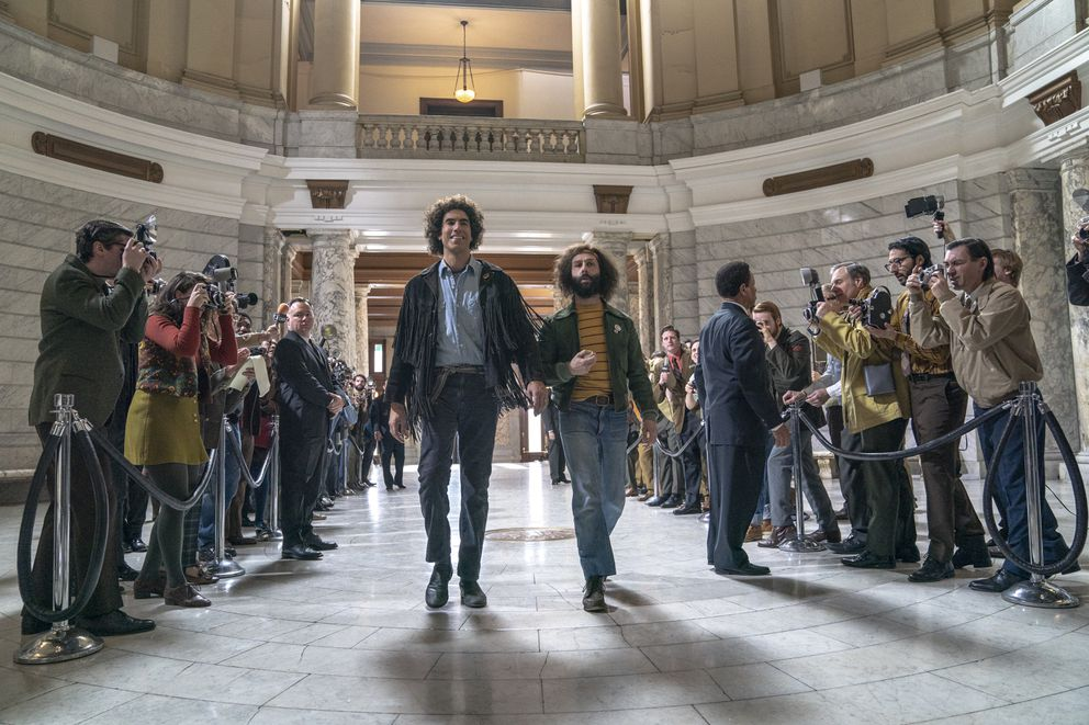 This image released by Netflix shows Sacha Baron Cohen, center left, and Jeremy Strong in a scene from 'The Trial of the Chicago 7. ' (Niko Tavernise/Netflix via AP)