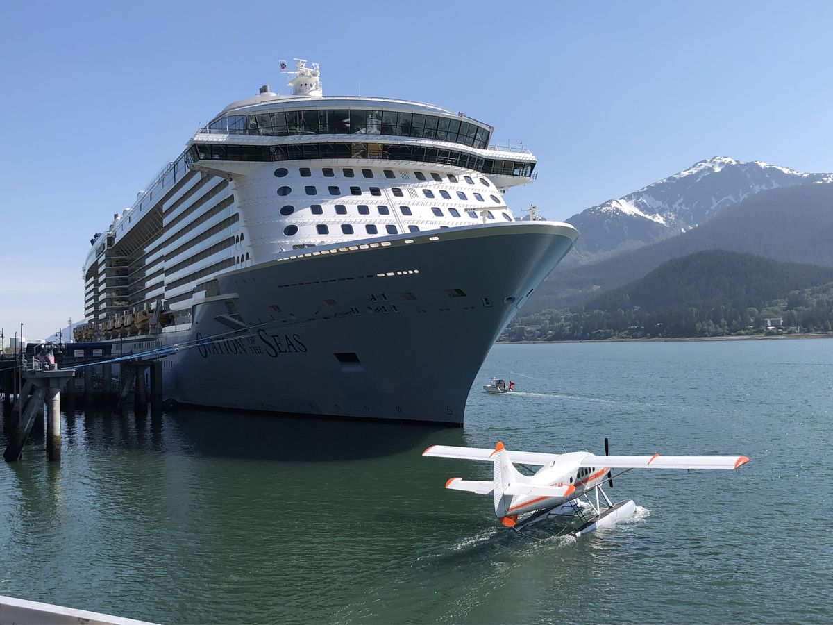 The cruise ship Ovation of the Seas is seen moored in the Port of Juneau on Sunday, May 26, 2019 as a floatplane taxis across the harbor. (James Brooks / ADN)