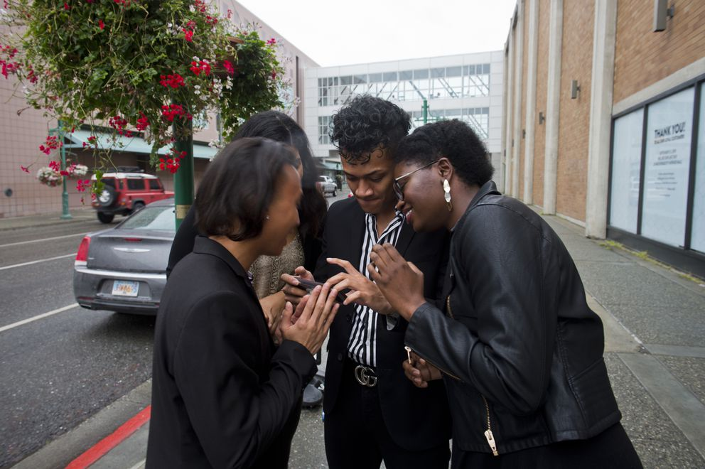 Nordstrom employees, from left, Justin Sangalang, Jackalynne Smith, Vave Graf and Asey Fowlis look at pictures they took outside the store on its last day in business. (Marc Lester / ADN)