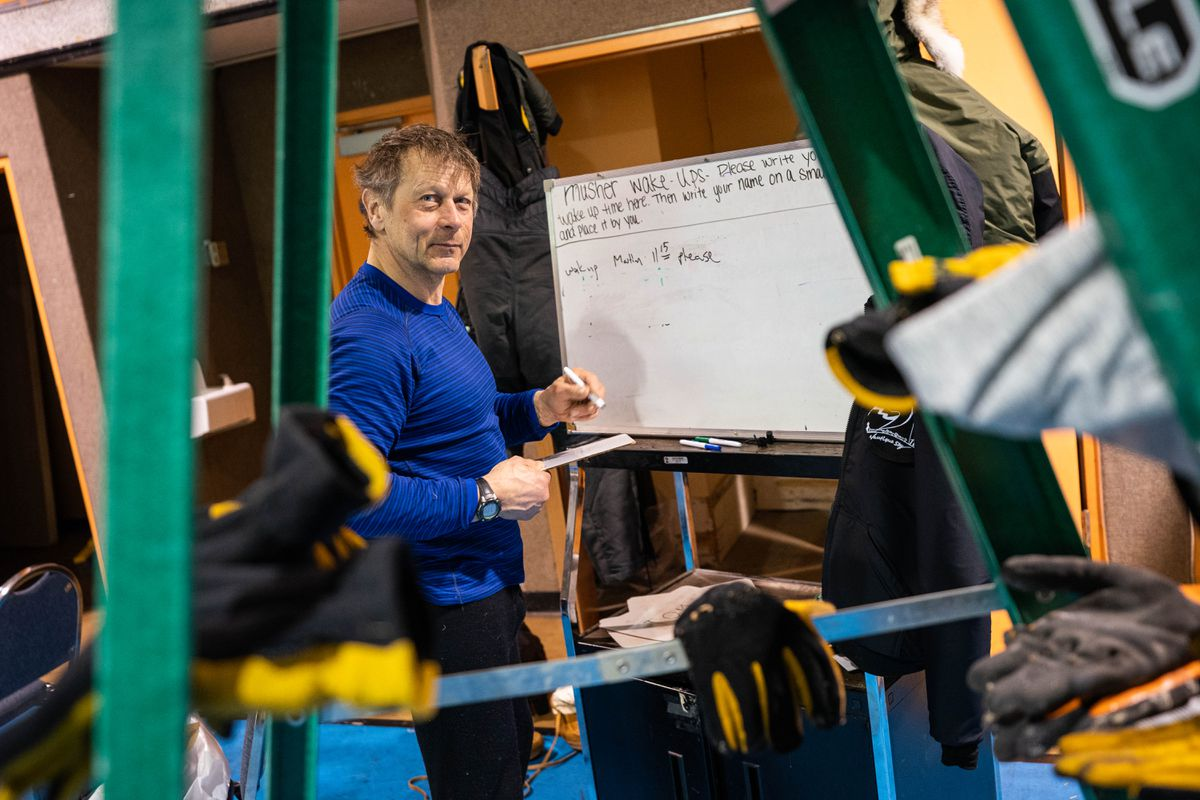 Martin Buser writes down his wake-up time on a whiteboard in the Nikolai checkpoint during this year's Iditarod. (Loren Holmes / ADN)