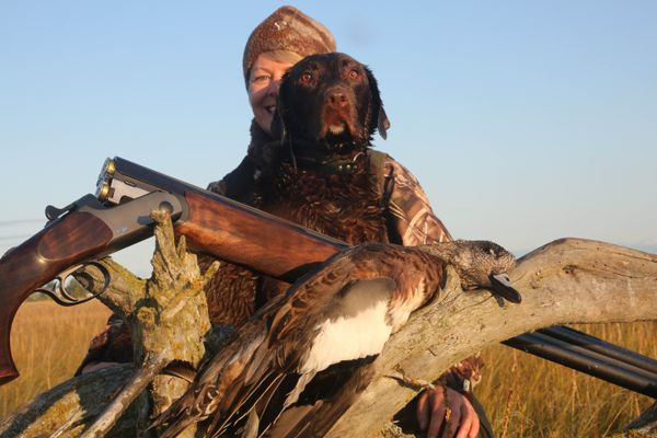 Christine Cunningham and her dog Cheyenne with a wigeon on the Kenai River Flats on Labor Day. (Steve Meyer)