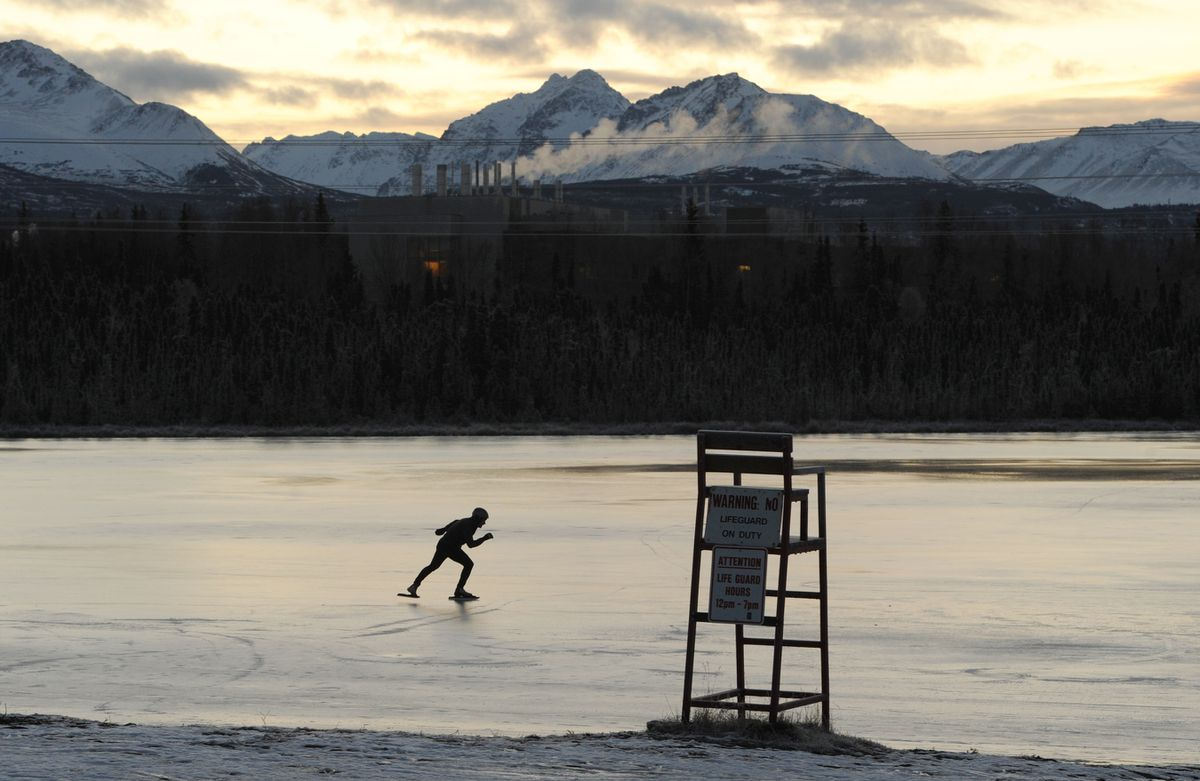 Peter Oswald glides across the ice on nordic blades while skating at Goose Lake before sunrise on Wednesday, Dec. 11, 2019. (Bill Roth / ADN)