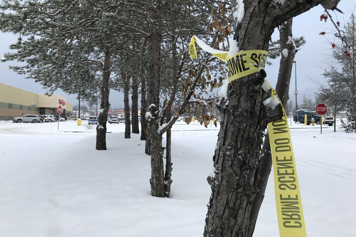 Crime scene tape remains Thursday morning near the Fred Meyer parking lot where a man was shot and killed late Wednesday night. (Bill Roth / Alaska Dispatch News)