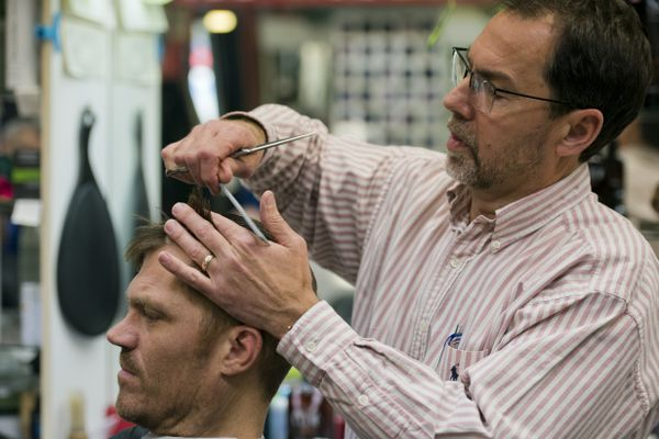 Scott Theis cuts Mark Renner's hair on Nov. 13, 2017, at A Cut Above barber shop in the Mall at Sears. (Marc Lester / Alaska Dispatch News)