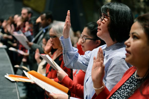 East High School teacher Yoko Grove raises her hand and repeats the Oath of Allegiance during a naturalization ceremony at East High School on April 23, 2019. (Marc Lester / ADN)