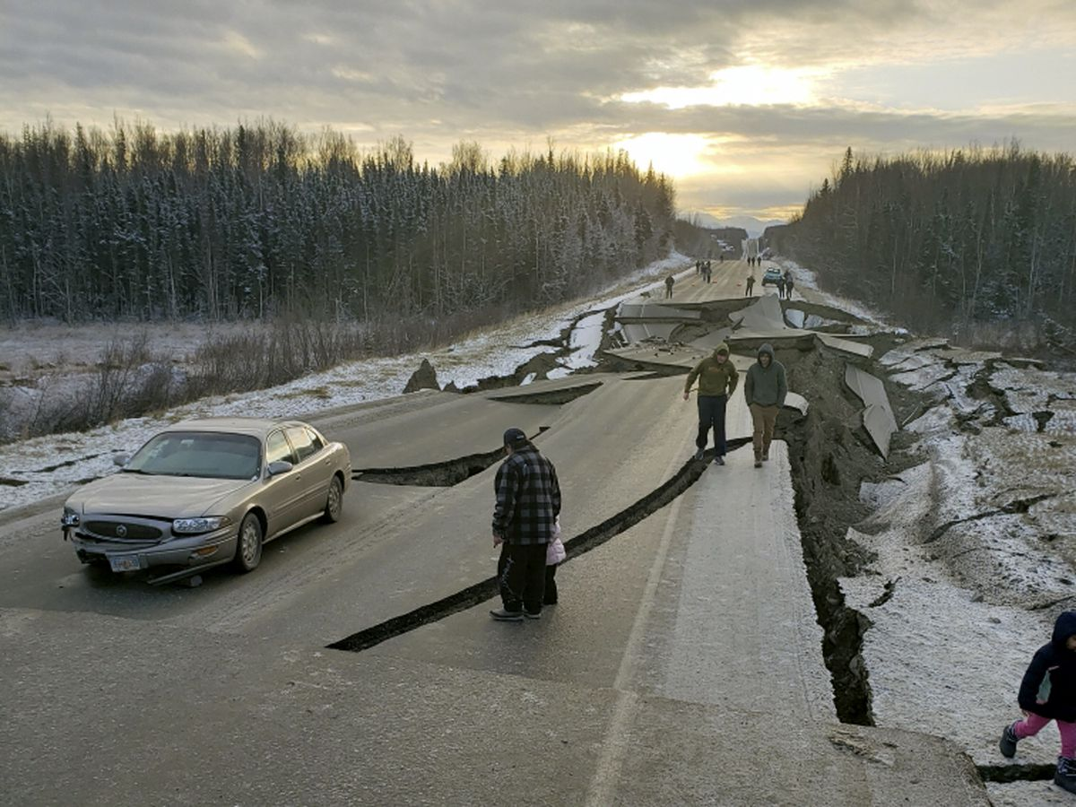 In this photo provided by Jonathan M. Lettow, people walk along Vine Road after an earthquake, Friday morning, Nov. 30, 2018, in Wasilla, Alaska. (Jonathan M. Lettow via AP)