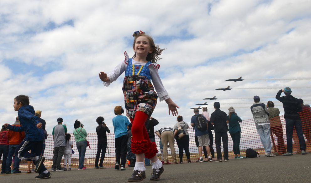 Hannah Grace Gentry, wearing her U.S. Marine Corp dress, pretends she is an airplane as the U.S. Navy Blue Angels pass by during the Arctic Thunder air show at Joint Base Elmendorf-Richardson on Saturday. (Bob Hallinen / Alaska Dispatch News)