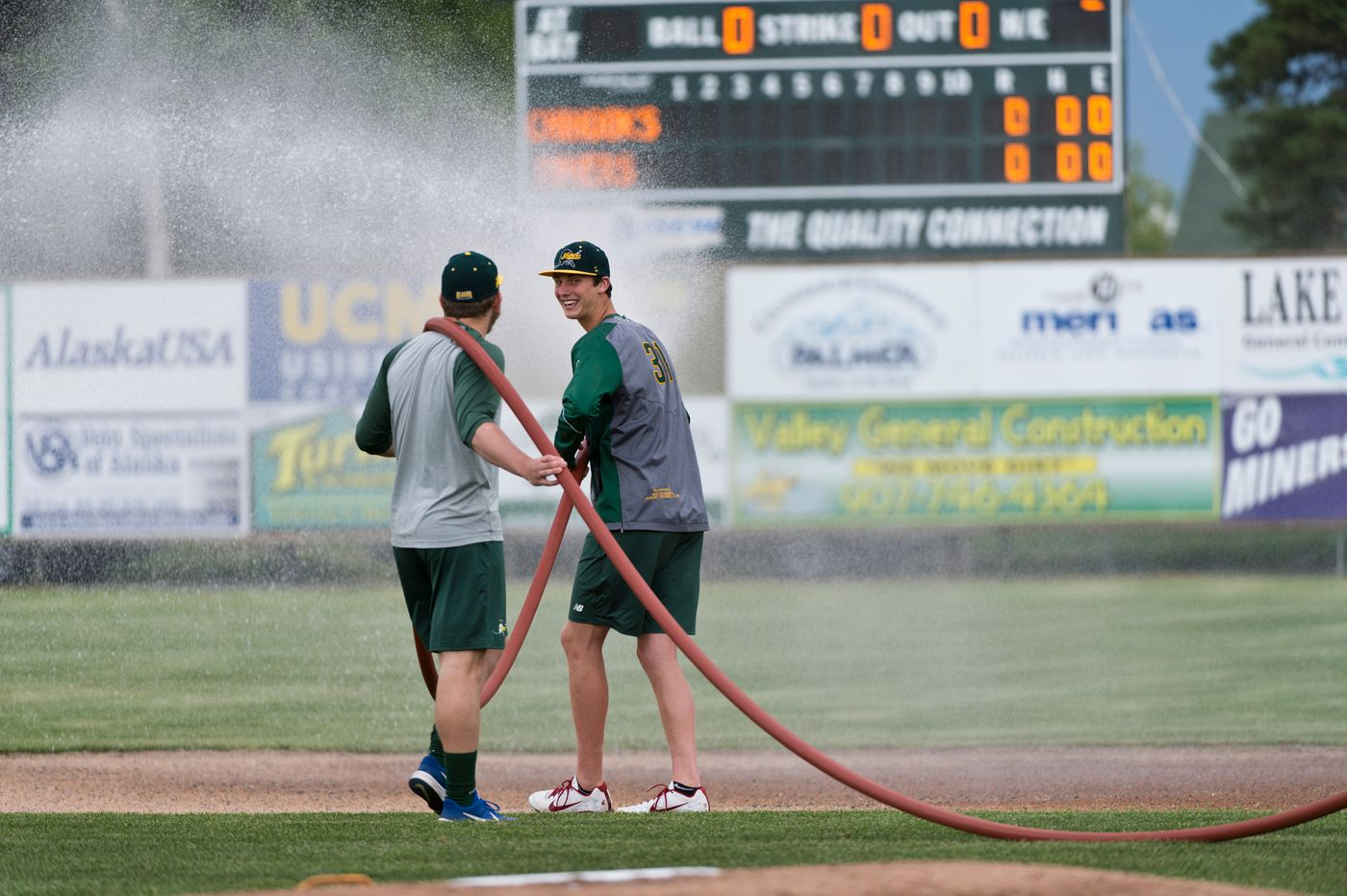 Miners players tend to the field before the season opener. (Marc Lester / ADN)