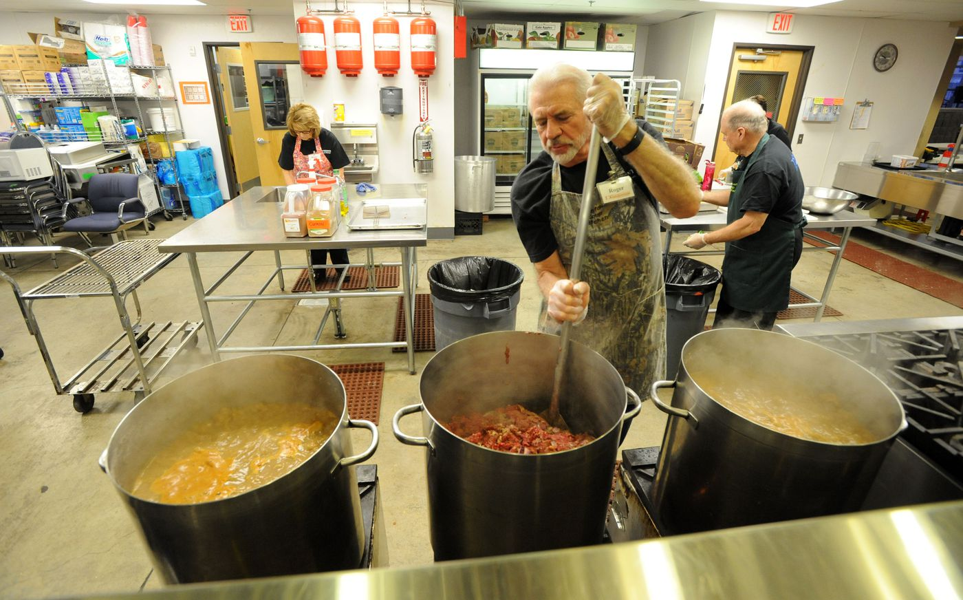 Beans simmer in the two outside pots, while Roger Morris, a 10-year volunteer with the Downtown Soup Kitchen, stirs the moose meat for Bullwinkle's Chili to serve for lunch, Thursday, Jan. 7. 20 lbs of donated road-killed moose hamburger was cooked into the chili.