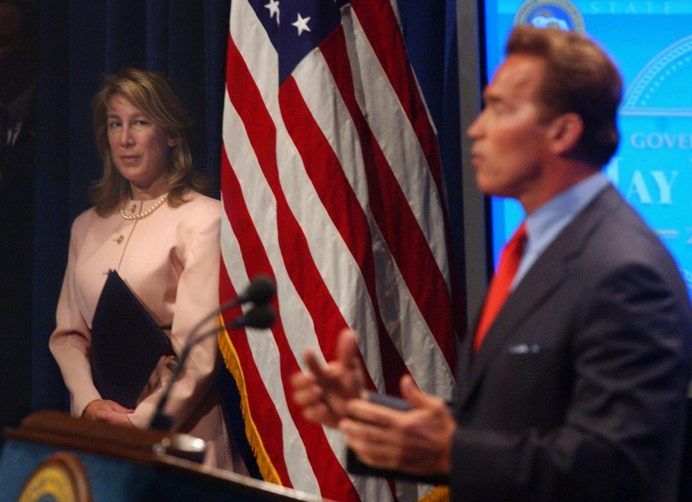 Then-California Finance Director Donna Arduin stands in the shadows as she watches Gov. Arnold Schwarzenegger discuss the revised 2004-05 state budget she helped craft, at a news conference in Sacramento, Calif., Thursday, May 13, 2004. (AP Photo/Rich Pedroncelli)