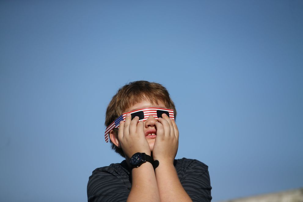 A boy uses solar viewing glasses as the sun emerges through fog cover before the solar eclipse in Depoe Bay, Oregon. REUTERS/Mike Blake