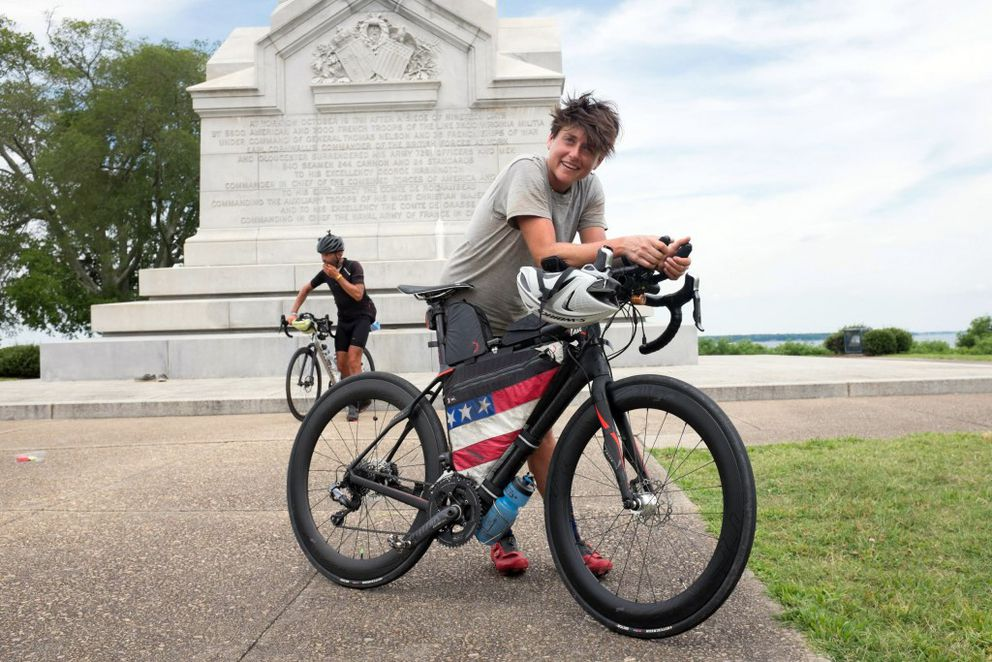 Lael Wilcox of Anchorage relaxes at the Yorktown Victory Monument after coming from behind on the final day to overtake Steffan Streich of Greece, back, to win the 4,200-mile Trans Am Bike Race. (Nicholas Carman)