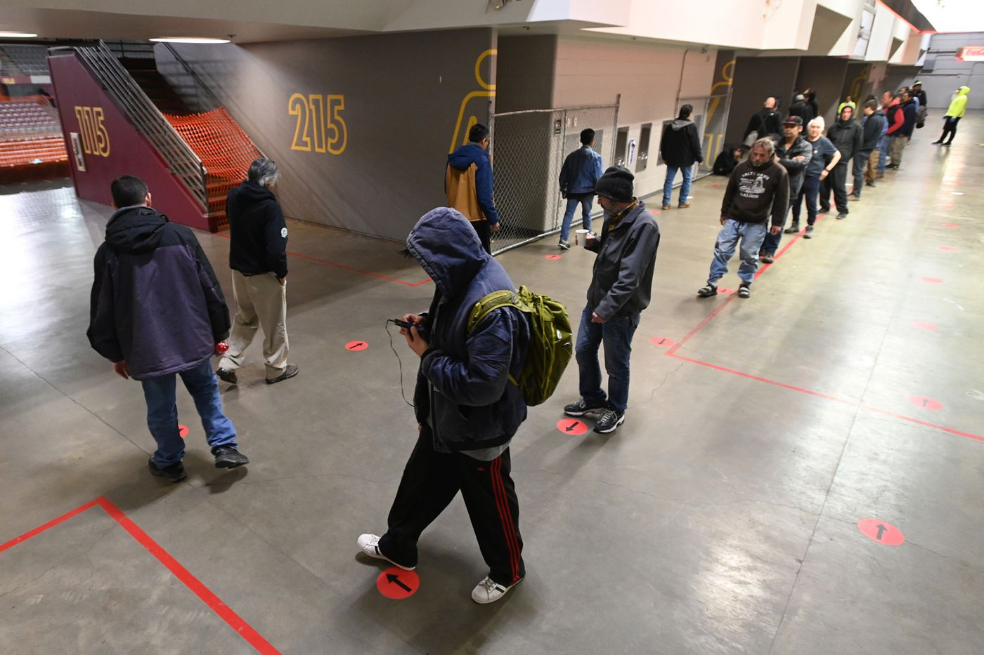 APRIL 29. Clients use dots on the floor to keep recommended social distance spacing while lunch is served at the Bean's Cafe emergency shelter inside the Sullivan Arena during the COVID-19 pandemic. (Bill Roth / ADN)