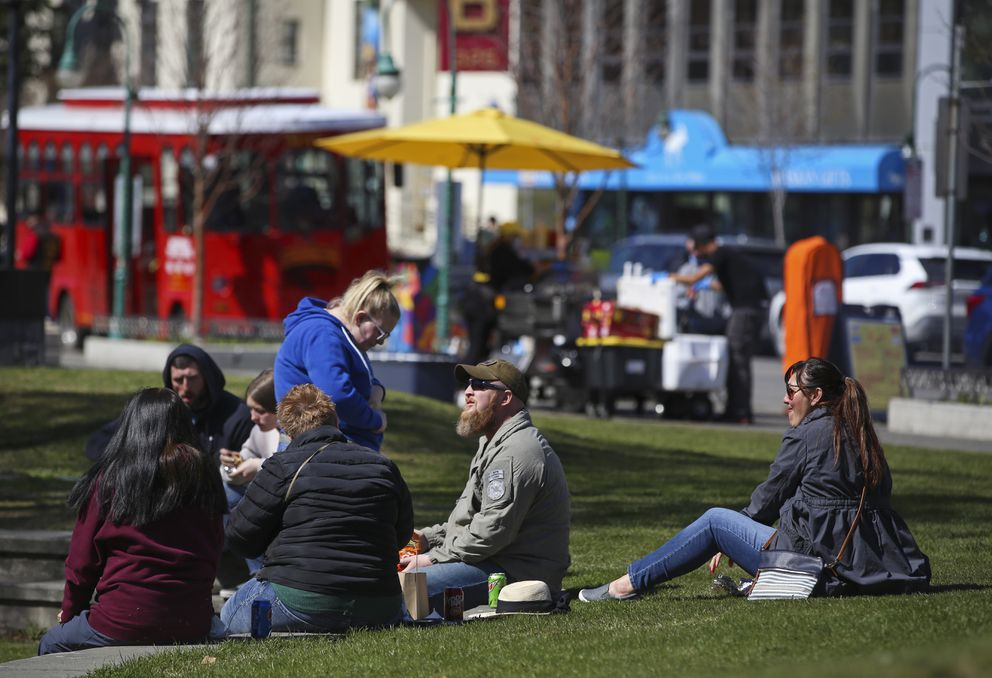 People sit in the grass in Peratrovich Park and eat lunch in downtown Anchorage on Thursday, May 13, 2021. (Emily Mesner / ADN)