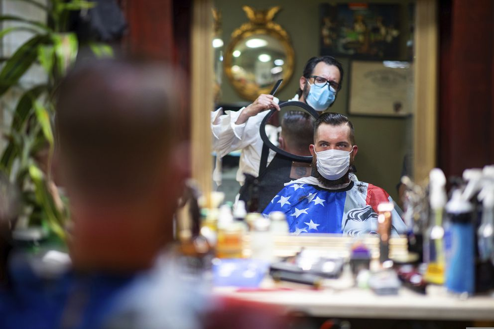 FILE - In this Friday, June 26, 2020 file photo, Barber Mike McAndrew holds a mirror as customer Rob Verrastro looks at his new haircut at Three Saints Barbershop and Shave Parlor in Jessup, Pa. (Christopher Dolan/The Times-Tribune via AP, File)