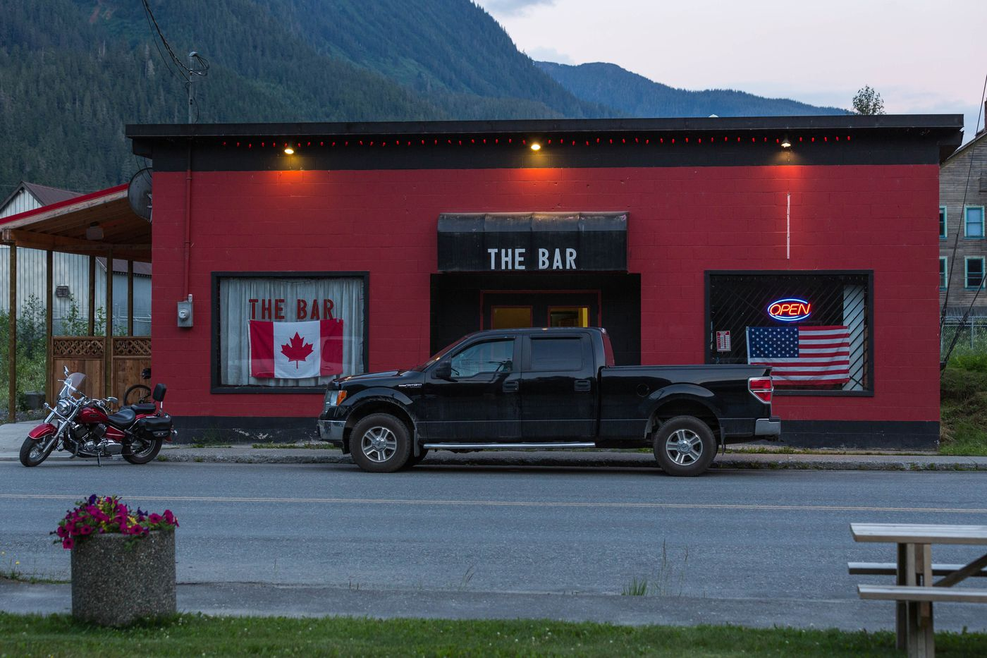 The Bar in Stewart, British Columbia displays both the Canadian and American flag on June 30, 2015. Stewart and Hyder, less than two miles apart, both benefit from shared tourism and mining economies, despite the barriers to trade across the international border.