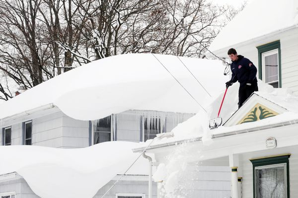 Andrew Zelak cleans the snow from his roof on Irving Place in Alden, N.Y. Thursday, Nov. 20, 2014.