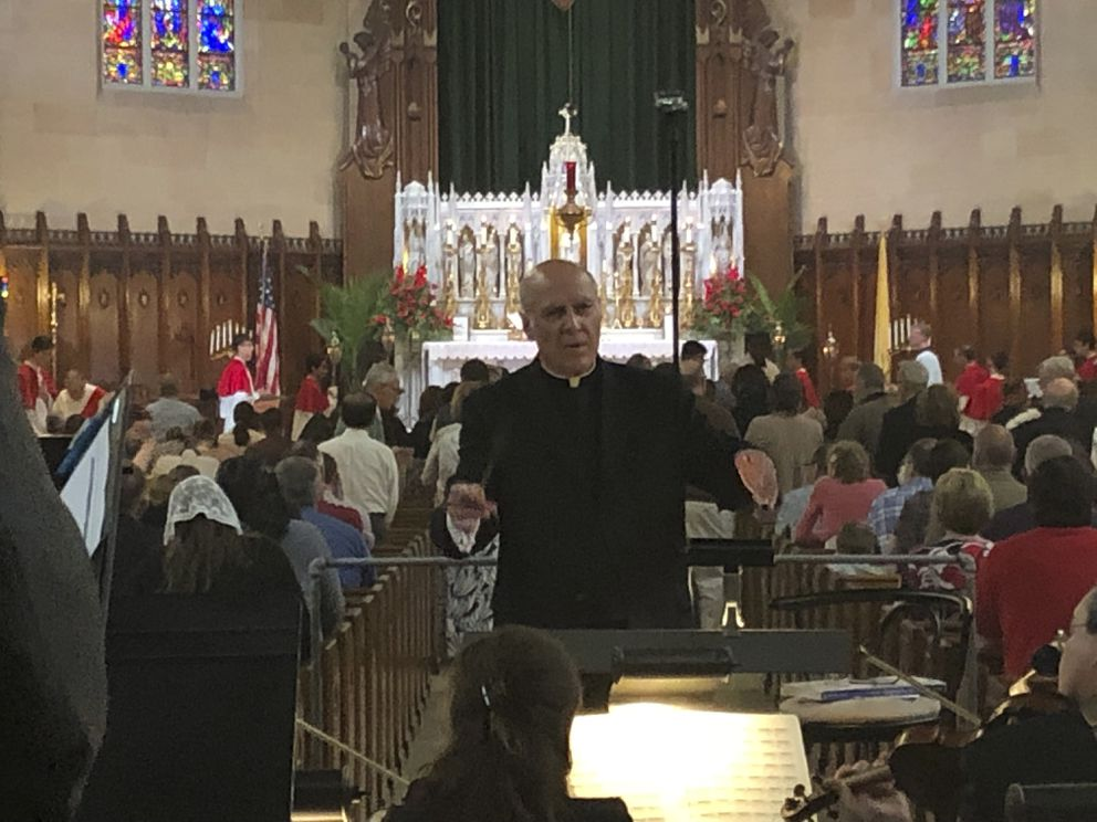 FILE - In this June 9, 2019 file photo, Father Eduard Perrone conducts a choir during a Mass at The Assumption of the Blessed Virgin Mary Church in Detroit. Perrone was a co-founder of a small nonprofit organization called Opus Bono Sacerdotii which has provided money, shelter, transport, legal help and other support to priests accused of sexual abuse. (AP Photo/Paul Sancya)
