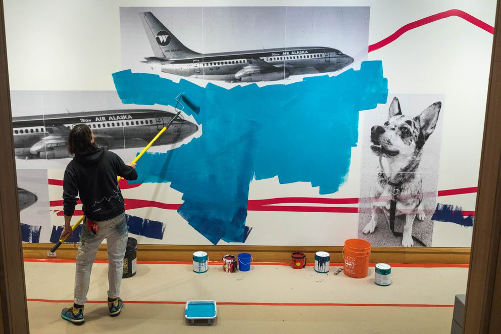 Artist James Temte works on a large mural in the Anchorage Museum atrium on Friday. Temte and assistant Nils Lane planned to complete the nearly 2,000-square-foot mural in two days. (Loren Holmes / Alaska Dispatch News)