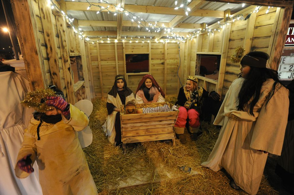 Sunnee Peters, Ricky Elliott, Keona Taylor, Mimi Peters and Leslie Carretero of the Christian Church of Anchorage gather around the baby Jesus in a living Nativity scene at the church. (Bob Hallinen / Alaska Dispatch News)