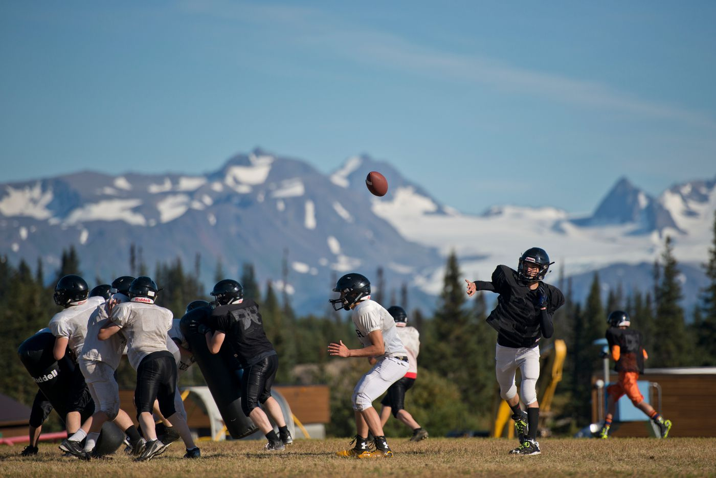 Quarterback Azary Reutov passes during Voznesenka's football practice on Thursday, Sept. 1. Because the team has only 16 players, it cannot practice full 11-on-11 plays. (Marc Lester / Alaska Dispatch News)