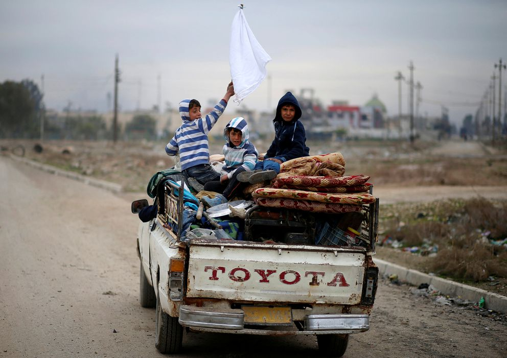 A displaced Iraqi boy holds a white flag as his family flees during the battle between Iraqi rapid response forces and Islamic State militants at Tigris river frontline between east and west of Mosul , Iraq, on Jan. 25. (Ahmed Jadallah/ Reuters)