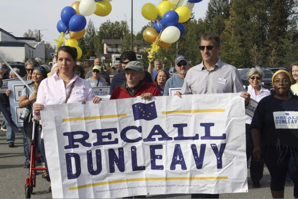 Meda DeWitt, left, Vic Fischer, middle, and Aaron Welterlen, leaders of an effort to recall Alaska Gov. Mike Dunleavy, lead about 50 volunteers in a march to the Alaska Division of Elections office in Anchorage, Alaska, on Thursday, Sept. 5, 2019. Recall organizers say they submitted 49,006 signatures in an attempt to force the recall election of the first-term governor. (AP Photo/Mark Thiessen)