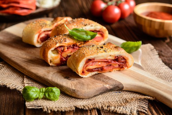 Traditional Italian Stromboli stuffed with cheese, salami, green onion and tomato sauce