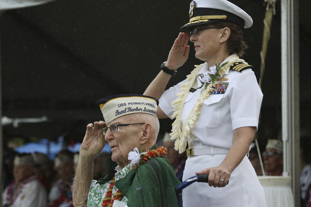 Everett Hyland, seated, who survived the attack on Pearl Harbor as a crew member of the USS Pennsylvania, salutes along with his granddaughter Navy Cmdr. Anna-Marie Fine on Friday, Dec. 7, 2018 as the USS Michael Murphy passes in Pearl Harbor, Hawaii during a ceremony marking the 77th anniversary of the Japanese attack. The Navy and National Park Service jointly hosted the remembrance ceremony at a grassy site overlooking the water and the USS Arizona Memorial. (AP Photo/Audrey McAvoy)