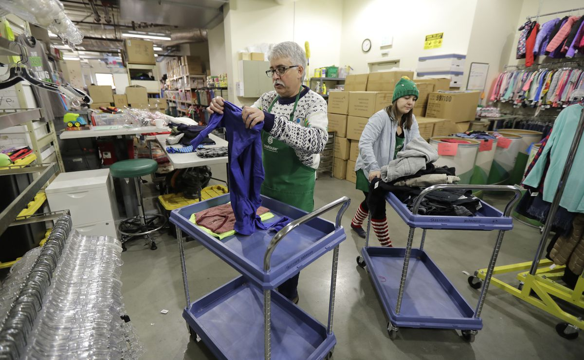 Chris Meyer, left, and Maddi Heim, fold and sort donated clothes at Treehouse, a nonprofit organization in Seattle that serves the needs of children in the foster-care system, on Dec. 21. The charity was one of several that received donations from the $11 million secret estate of Alan Naiman. (AP Photo/Ted S. Warren)