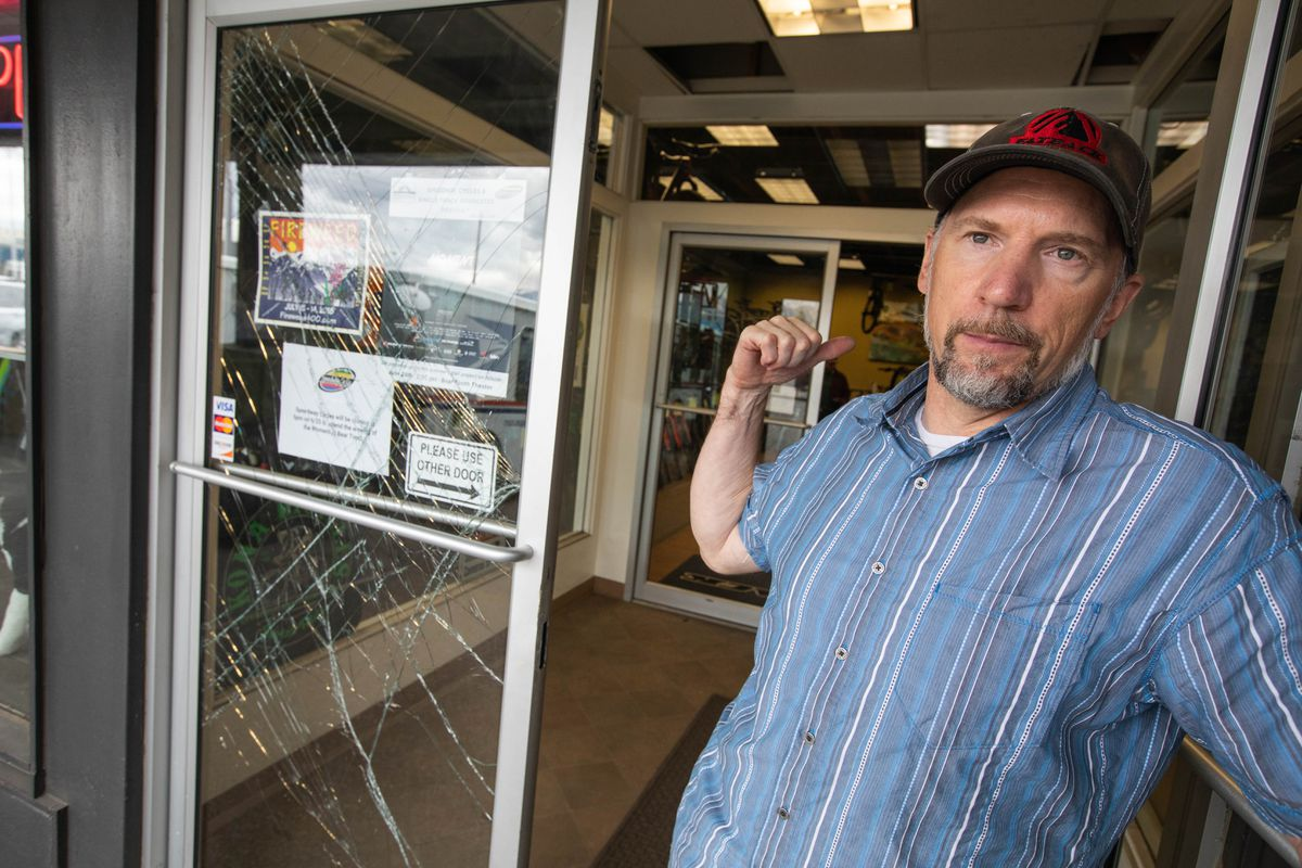 Speedway Cycles owner Greg Matyas stands next to the broken door to his shop Thursday. (Loren Holmes / ADN)