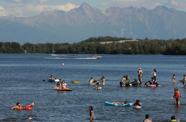 Sunbathers at Newcomb Park wade in Wasilla Lake during a sunny day. (Bill Roth / ADN