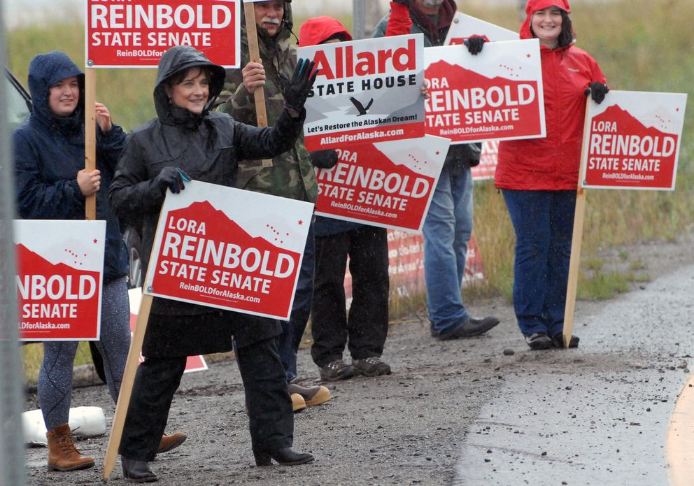 Lora Reinbold, in black, waves to cars at the Hiland Road exit off the Glenn Highway on Tuesday. (Matt Tunseth/Chugiak-Eagle River Star)