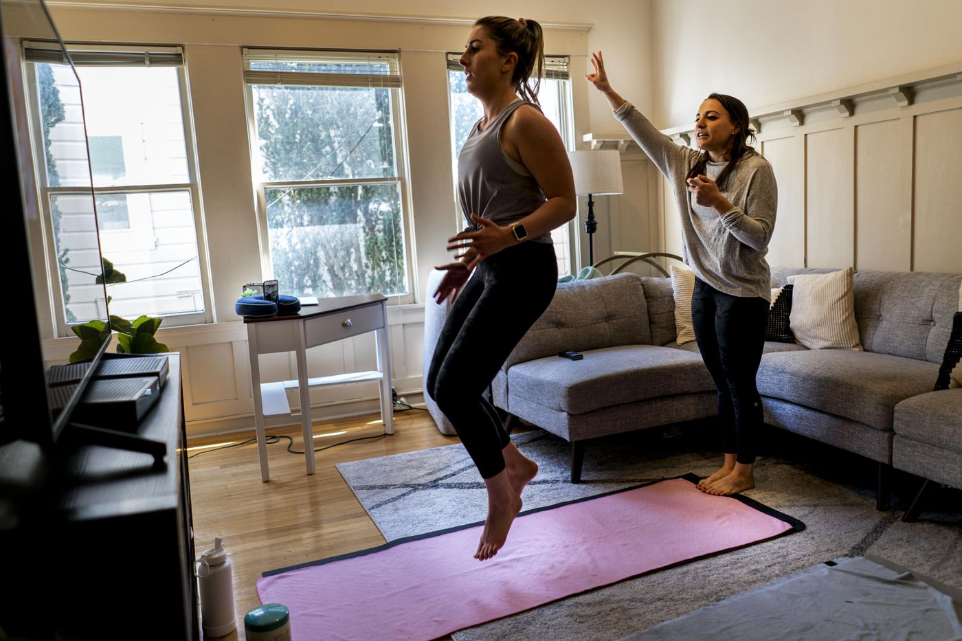 Pilates instructor Carley Henning teaches a streaming class from her apartment March 20 in the Marina District, with help from her roommate. Washington Post photo by Melina Mara